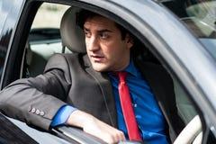 安全地驾驶他新的汽车的英俊的人 图库摄影