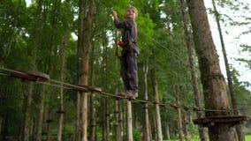 安全带的小男孩在一条路线上升在森林冒险公园 他在高绳索足迹上升 ?? 股票录像