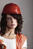 安全帽和橙色背心的性感的女孩 库存照片