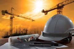 安全帽和建筑师pland在木桌上与日落scen 库存图片