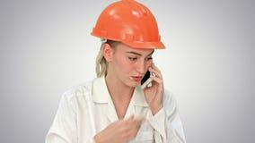 安全帽的呼喊恼怒的妇女的建筑工人,谈话在白色背景的智能手机 影视素材