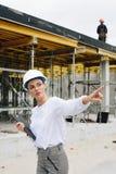 安全帽的年轻工程师有剪贴板的,指向手指,当站立时 免版税库存照片