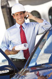 安全帽的生意人建筑师在移动电话 免版税库存照片