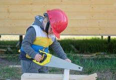 安全帽的男孩有锯一个木板的手锯的 免版税库存照片