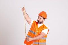 安全帽的建筑工人与测量T一起使用 库存照片