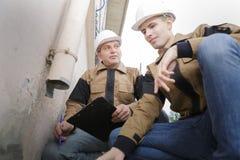 安全帽维护的管子的水管工房子外 图库摄影