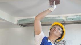安全帽铺沙的墙壁的微笑的建造者女性户内在建造场所 股票视频