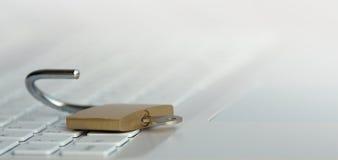 安全概念,打开在白色键盘的挂锁 免版税库存照片
