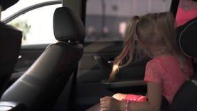 安全游乐器具紧固与母亲和女儿的儿童汽车座椅 佩带夏天明亮生动的年轻白种人白妈妈 股票录像