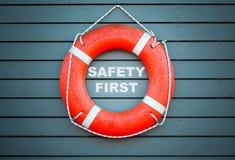 安全第一红色lifebuoy垂悬在蓝色墙壁上 图库摄影
