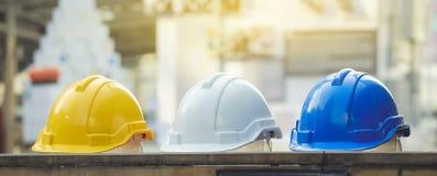 安全项目的白色,黄色和蓝色坚硬安全帽帽子 库存照片