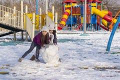 安卡拉/土耳其1月01日2018年:两个女孩在冬天滚动一个大和重的雪球修造一个雪人在戏剧地面 图库摄影
