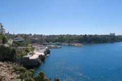 安塔利亚美丽的港口有帆船、Fisher小船、峭壁和城市墙壁的 库存照片