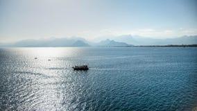 安塔利亚,土耳其- 2013年10月16日:在安塔利亚外面老港口的一个小船航行  免版税库存照片