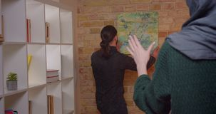安定在一栋最近被买的公寓的年轻有吸引力的回教夫妇特写镜头射击户内 挂图片的人  股票视频