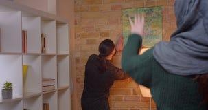 安定在一栋最近被买的公寓的年轻有吸引力的阿拉伯夫妇特写镜头射击户内 挂图片的人  股票视频