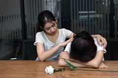 安慰一个哀伤的沮丧的女性朋友的可爱的亚裔妇女 破坏或最佳的关系概念 免版税库存图片