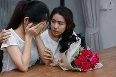 安慰一个哀伤的沮丧的女性朋友的被用尽的被注重的亚裔妇女 破坏或最佳的关系概念 免版税库存照片