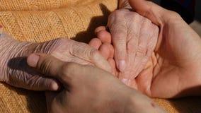 安慰一个年长对祖母室外关闭的手的年轻人男性手  影视素材