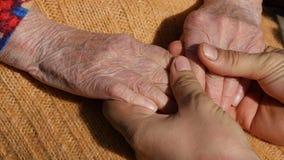 安慰一个年长对祖母室外关闭的手的年轻人男性手  股票录像