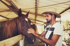 安慰一匹马的年轻马交配动物者在槽枥 免版税库存照片