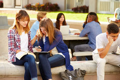 安慰不快乐的朋友的女性高中学生 免版税图库摄影