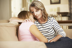 安慰十几岁的女儿的母亲在家坐沙发 免版税库存照片
