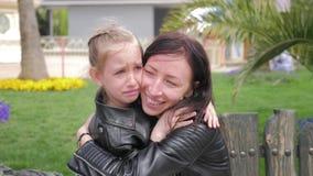 安慰和拥抱哭泣的女婴的俏丽的母亲 美丽的年轻母亲在公园镇定哭泣的女儿 股票录像