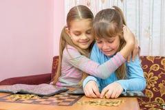安慰哭泣的妹妹的更老的姐妹,收集堆硬币 库存照片
