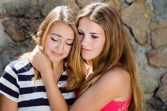 安慰哭泣的朋友的十几岁的女孩 免版税库存图片