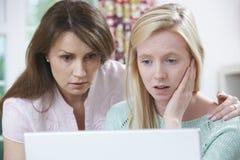 安慰女儿的母亲欺骗通过在网上胁迫 库存图片