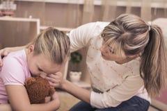 安慰她哀伤的十几岁的女儿的母亲 少年问题 可安慰的女儿她的母亲 免版税库存图片