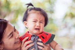 安慰她的哀伤亚洲女婴哭泣和母亲 免版税图库摄影