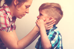 安慰她的小哭泣的孩子的年轻母亲 免版税库存照片