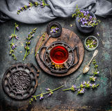 安慰性的杯子与最新鲜的有机成份的清凉茶:草本和花在土气葡萄酒背景与茶工具 图库摄影