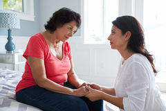 安慰母亲的成人女儿遭受以老年痴呆 免版税库存图片