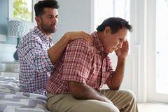 安慰父亲的成人儿子遭受以老年痴呆 免版税库存照片