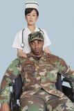 安慰轮椅的女性护士失去能力的美国陆战队战士在浅兰的背景 图库摄影
