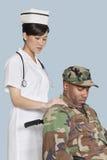 安慰轮椅的女性护士失去能力的美国陆战队战士在浅兰的背景 免版税库存照片