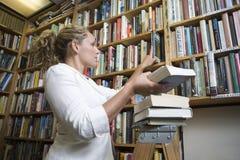 安排书的图书管理员在图书馆 免版税库存照片