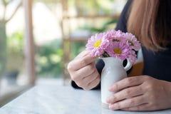 安排在一个白色小花瓶的妇女美丽的桃红色花在桌上 免版税库存照片