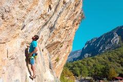 安排在岩石的成熟登山人套住在森林和村庄上 免版税图库摄影