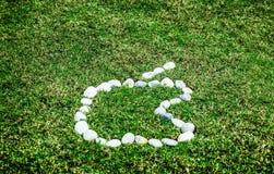 安排在绿草的白色石头在苹果商标概念f 免版税库存照片