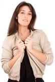 安排她的夹克的微笑的俏丽的浅黑肤色的男人 免版税库存图片