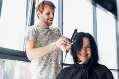 安排年轻美丽的妇女她的头发被剪在美发师` s 享受做一种新的发型的过程 库存照片