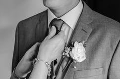 安排新娘的新郎他的领带调整由他的母亲 免版税库存照片