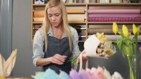 安排现代花束和完成它与完善的丝带的女性白肤金发的卖花人 英俊的花店所有者工作 影视素材