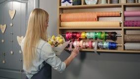 安排现代花束和选择它的女性白肤金发的卖花人完善的丝带结合不同的颜色 股票录像