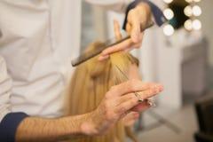 安排的年轻女人她的发型由美发师 库存照片