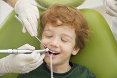 安排的男孩他的牙审查由牙医 免版税库存图片